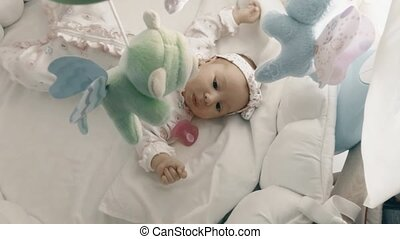 Playful newborn baby girl in her cot - Newborn baby girl in...