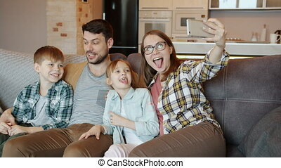 Playful people mom dad boy and girl posing for smartphone camera with funny faces laughing at home