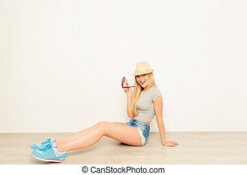 Playful pretty girl in hat sitting on floor and holding glasses