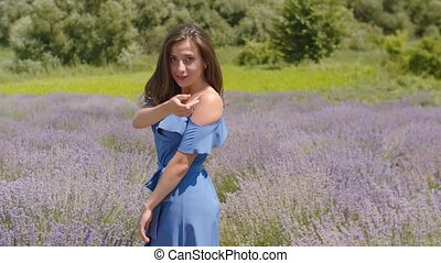 Playful pretty woman beckoning in summer nature