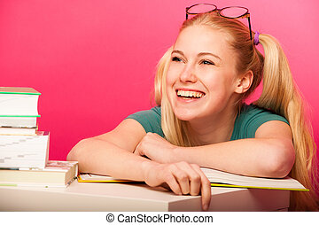 Playful schoolgirl with two hair tails and big eyeglasses leaning on small table full of books laughing.