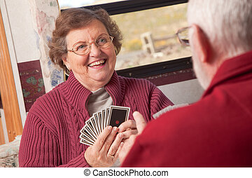 Happy Senior Adult Couple Playing Cards in Their RV.