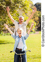 playful senior couple having fun riding bicycle outdoors