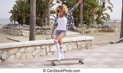 Playful sexy young woman posing with a skateboard on a paved...