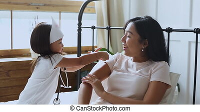 Playful smiling vietnamese ethnic woman playing clinic with ...