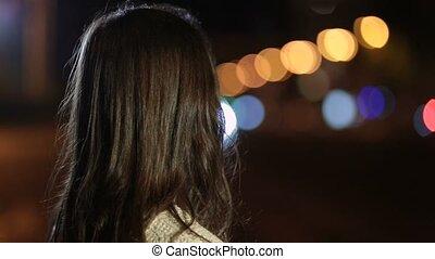 Playful smiling woman flirting on street at night - Portrait...