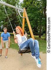 Playful teenage couple girl on swing