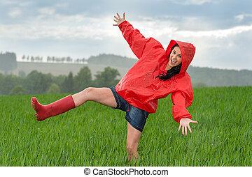 Playful teenage girl dancing in the rain