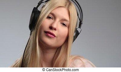 Playful teenage girl with earphones on white