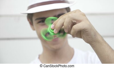 Playful teenage man having fun with hand fidget spinner...