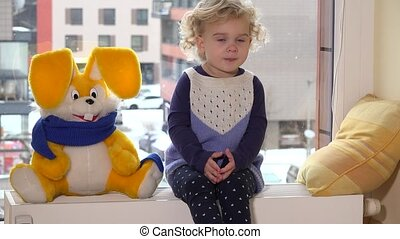 playful toddler girl sitting near window with friend bunny. Winter snow falling