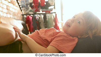 Playful toddler lying on sofa - Side view of adorable blond...