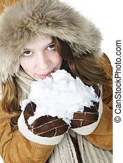 Playful winter girl holding snow