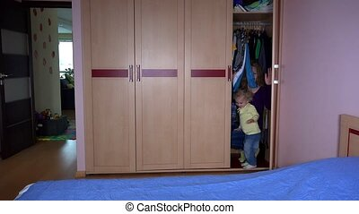 Playful woman and her daughter girl get out from closet and run away.