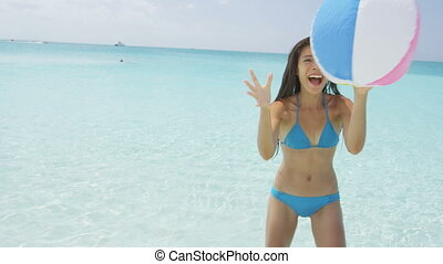 Playful young woman catching ball on beach. Cheerful female in blue bikini enjoying while standing in water. Attractive woman is on her summer vacation. SLOW MOTION RED EPIC.