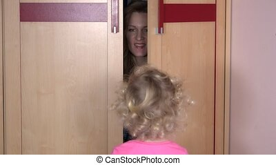 Playful woman hiding from daughter child in wardrobe closet at home