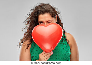 playful woman holding red heart shaped balloon
