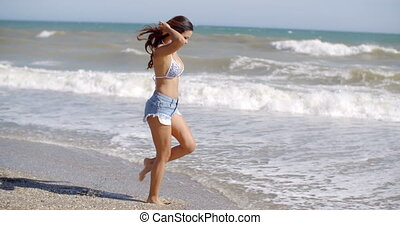 Playful woman playing in the surf on a beach