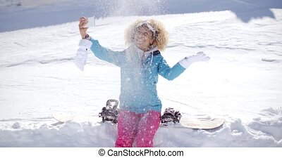 Playful woman posing for a selfie in the snow