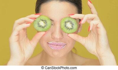 Playful woman with kiwi fruit eyes