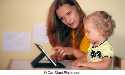 Playful woman with toddler daughter girl using tablet computer