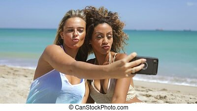 Playful women posing for selfie on beach - Confident...