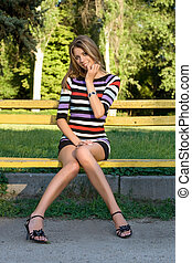 Playful young blonde sitting on a park bench