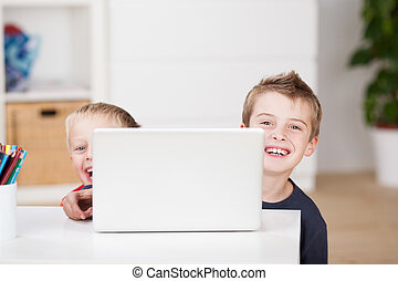 Playful young boys using a laptop computer - Two playful...