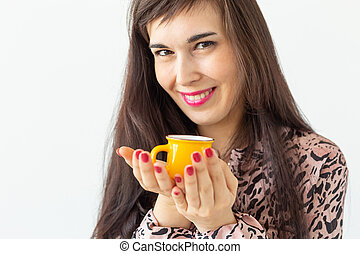 Playful young brunette woman holding in her hands a small yellow mug posing on a white background