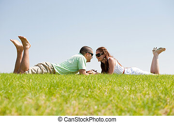 Playful young couple laying on a grass lawn