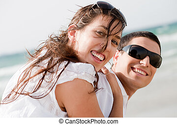 playful young couple look back and smiling on the beach, ...