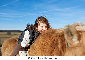 Playful young girl amused while riding her horse laying on...