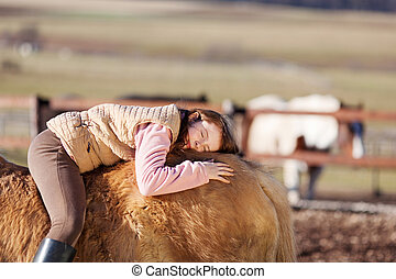 Playful young girl laying in her horse