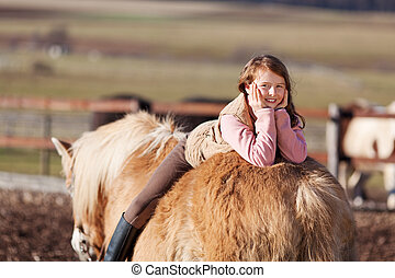 Playful young happy girl laying in her horse
