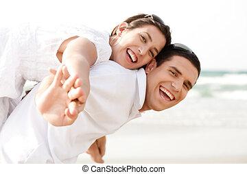 Young man piggybacking his girlfriend at beach