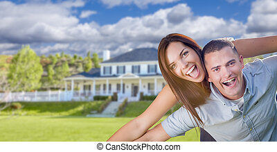 Playful Young Military Couple Outside Beautiful Home -...
