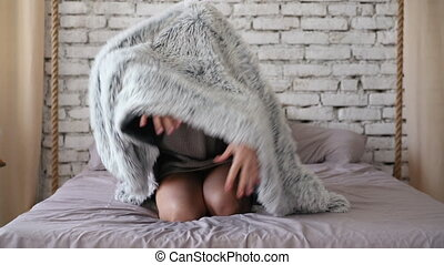 Playful young woman hiding under blanket and have fun in bed...