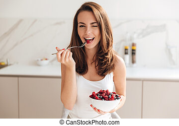 Playful young woman holding bowl with fresh berries while...