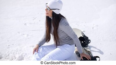 Playful young woman throwing a snowball as she sits with her...