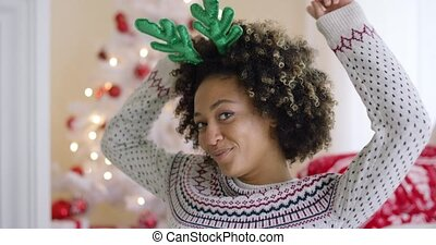 Playful young woman wearing green reindeer antlers grinning...