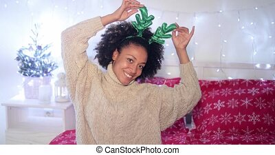 Playful young woman wearing green reindeer antlers to...