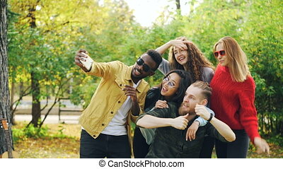 Playful youth men and women are taking selfie in park using smartphone, making funny faces and wearing sunglasses standing outdoors and laughing. Fun and nature concept.