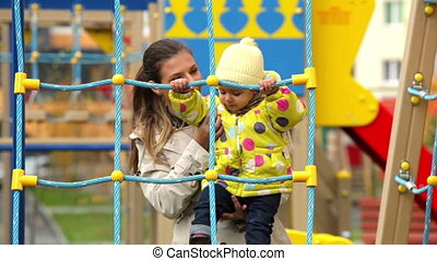 Playground activity - Mother helping her active daughter to...