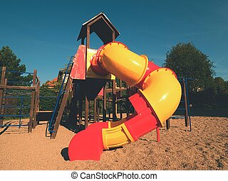 Playground colorful tube slide in public park. New slider tube and wooden ladders