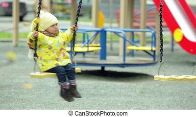 Playground fun - Charming kid having fun swinging on the...