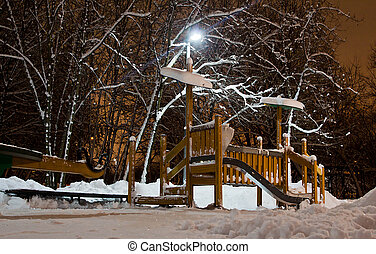 playground in the park in the winter evening