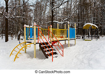 Playground in the winter park covered with snow.