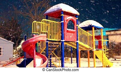 Playground, loop - Colorful playground in snowfall night....