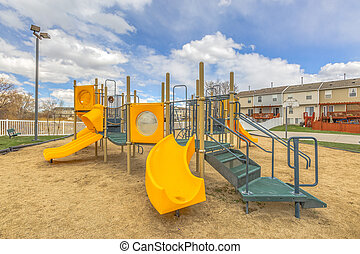 Playground with a bright yellow slide under the vivid sky with puffy clouds