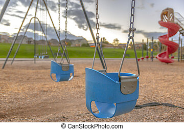 Playground with baby swing and slide near homes